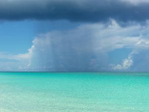 Rain shower over the white and blue beaches of Bimini, The Bahamas.