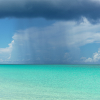 Rain shower over the white and blue beaches of Bimini, The Bahamas.